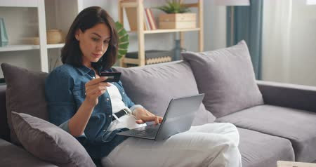 легкий : Pretty girl is making online payment holding bank card using modern laptop at home sitting on sofa and smiling. Finance, shopping in internet and youth concept.