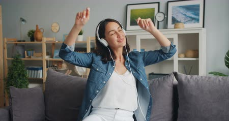 flat head : Joyful woman in headphones is listening to music moving hands and head dancing sitting on sofa at home relaxing. Modern youth, flat and lifestyle concept. Stock Footage