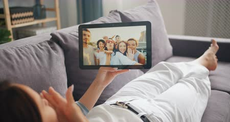 wi fi : Happy girl is using tablet to make video call talking to friends online from house lying on couch enjoying communication sending air kiss. Friendship and technology concept.