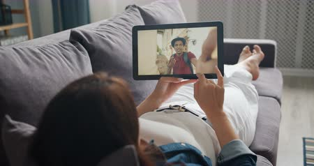 hírnök : Student talking to boyfriend online making video call with tablet lying on sofa in cozy apartment enjoying communication. Millennials and devices concept.