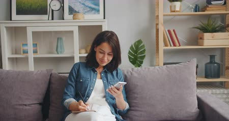hírnök : Young woman student is holding smartphone looking at screen and writing in notebook sitting on sofa at home. Modern technology, people and apartment concept.