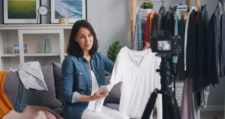 describing : Slow motion of joyful fashion vlogger recording video describing clothes then sending air kiss and waving hand using professional camera. Style and blogging concept.