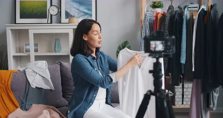 describing : Female stylist attractive young woman is recording video about modern clothes for interner vlog using camera at home. Blogging, style and people concept. Stock Footage