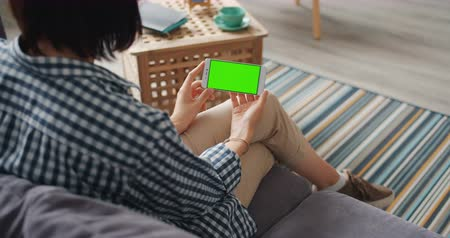 hírnök : Young woman is using smartphone with green mock-up screen sitting on sofa at home enjoying modern technology. Gadgets, application and template concept. Stock mozgókép