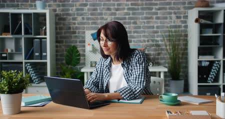 informal : Slow motion of attractive young woman in casual clothing working with laptop sitting at desk in office alone concentrated on work. People and business concept.