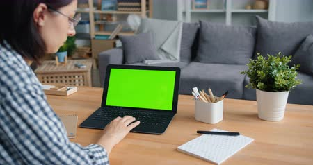 portable information device : Young woman is using laptop with green mock-up screen at table at home touching touchpad enjoying media content. Tehnology, people and house concept.