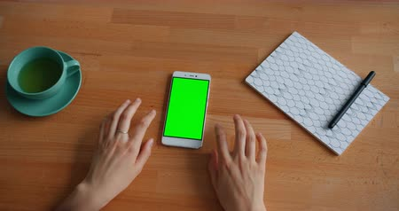 lupetto : Slow motion of womans hands moving on table with green mock-up screen smartphone modern gadget. Cup of tea and beautiful notebook are visible on desk. Filmati Stock
