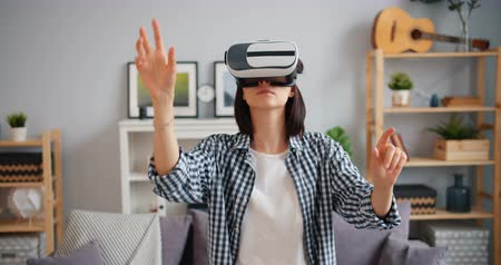 flat head : Female student is moving arms turning head using augmented reality glasses in house focused on amazing activity. Millennials and new technology concept. Stock Footage