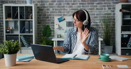 informal : Young lady in headphones is working with laptop listening to music moving head and hands in office. Break, happy youth, modern entertainment concept. Stock Footage
