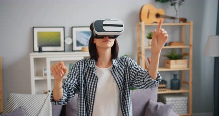 flat head : Young lady in headset is moving hands and head wearing virtual reality glasses at home having fun with hi-tech gaming equipment enjoying modern technology.