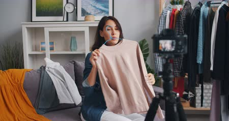ajánlás : Female vlogger fashion designer recording video about fashionable clothes looking at camera on tripod and talking holding garment. Occupation and blog concept. Stock mozgókép
