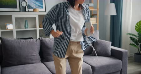 crazy girl : Joyful young lady is listening to music in headphones dancing having fun at home enjoying song and leisure time holding smartphone. Gadgets and people concept.