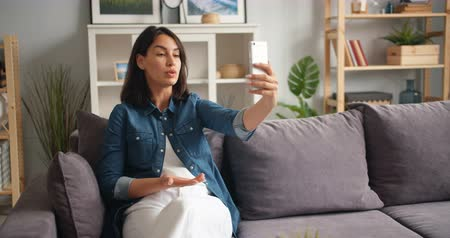 hírnök : Unhappy girl in casual clothing is talking gesturing making online video call with smartphone at home complaining looking at screen with angry and sad face.