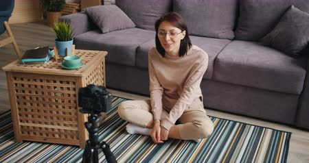 fikirler : Female blogger attractive young woman is recording video at home talking and gesturing using camera sitting on floor. Modern youth, occupation and house concept. Stok Video