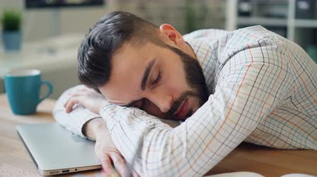 olhos fechados : Close-up of handsome young businessman sleeping in office lying on laptop on desk relaxing resting. Break at work, tired youth and heavy overwork concept. Stock Footage