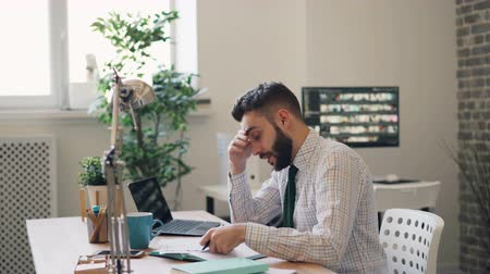 мрачный : Stressed guy businessman is reading business contract shaking head throwing pen sitting at table in office room. Problems at work and negative emotions concept. Стоковые видеозаписи