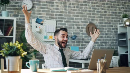vaření v páře : Seamless loop of happy businessman smiling with raised arms looking at laptop screen at desk in offce enjoying success while cup of coffee steaming on table.