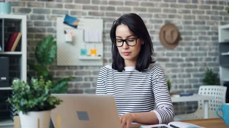 独立した : Portrait of beautiful busineswoman in glasses working with laptop then smiling looking at camera sitting at desk busy with work. People and occupation concept.
