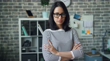 personalidade : Portrait of independent girl with black hair and trendy eyeglasses standing in office with arms crossed looking at camera. People, job and workplace concept.