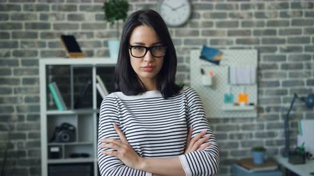 стремление : Portrait of beautiful office worker looking at camera standing with arms crossed in loft style room with serious face. People, occupation and confidence concept. Стоковые видеозаписи