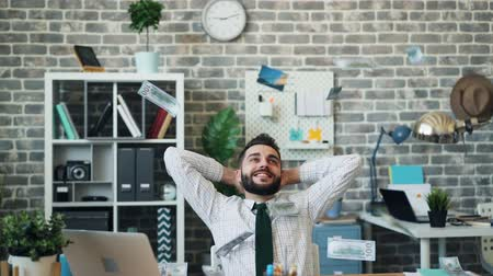 lucrative : Slow motion of cash falling on excited entrepreneur sitting at table in office smiling enjoying money and wealth. Rich people, happiness and workplace concept. Stock Footage