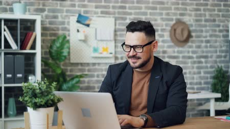 kariyer : Portrait of attractive entrepreneur joyful guy in jacket and glasses using laptop then looking at camera smiling. Business people and modern technology concept. Stok Video