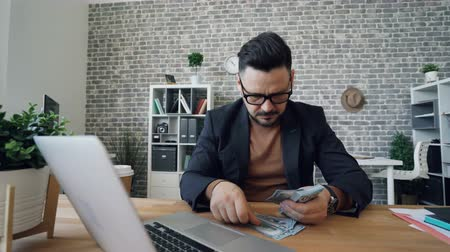 rachunkowość : Rich entrepreneur handsome brunet in glasses is counting money smiling sitting at office table at work. Finance, wealthy people and salary concept. Wideo