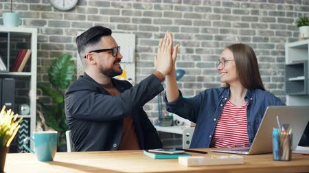five : Cinemagraph loop of happy colleagues man and woman doing high-five sitting at table in office while cup of hot tea is steaming on desk. People and work concept.