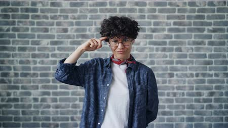 houding : Portrait of attractive girl twisting finger at head making fool sign looking at camera standing alone on brick wall background. People and attitude concept. Stockvideo
