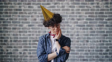 cheerless : Portrait of unhappy birthday girl in party hat standing with crossed arms and sad face on brick background. Bad mood, disappointing holidays and sadness concept.