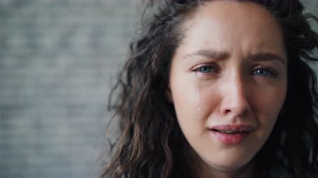 bad looking : Close-up portrait of unhappy young girl crying on brick wall background sobbing with sad face feeling bad. Negative emotions, unhappiness and tears concept. Stock Footage