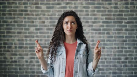 umutlu : Portrait of scared girl making praying hands gesture speaking standing alone on brick wall background. Hope for the best, people and human belief concept.