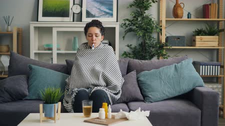 infectious : Shivering girl student taking body temperature sitting with thermometer in mouth covered with blanket on sofa at home. People, house and healthcare concept.
