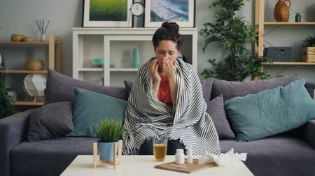 nešťastný : Sick young woman coughing drinking medicine sitting on couch at home covered with warm blanket. Unhealthy people, medical problems and apartment concept.