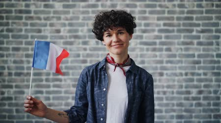 orgulho : Slow motion portrait of French lady holding official flag of France and smiling looking at camera standing on brick wall background. People and countries concept.