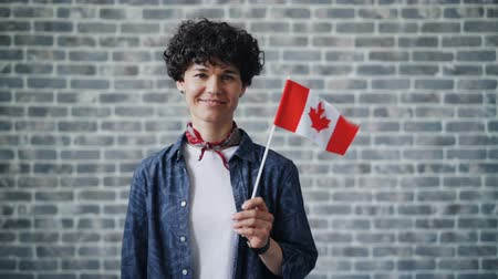 drapeau canadien : Slow motion portrait of cute young female student holding Canadian flag on brick background smiling looking at camera. People, nation and world concept.