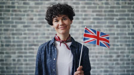 гражданство : Slow motion portrait of attractive lady holding British flag on brick wall background looking at camera and smiling. Patriots, countries and youth concept.