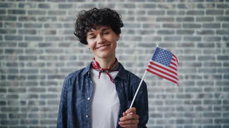 гражданство : Slow motion of proud American citizen attractive young woman holding US flag smiling on brick background. United states of America, world and youth concept.
