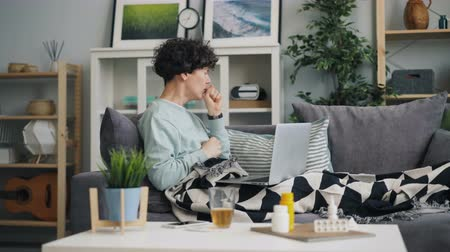 cheerless : Woman with sore throat is using laptop looking for information about disease browsing sitting on couch at home. Healthcare, modern technology and youth concept. Stock Footage