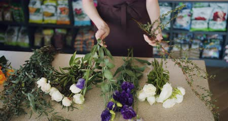букет : Slow motion of female florist young woman in apron holding beautiful flowers making bouquet working in shop. Small business, profession and plants concept.
