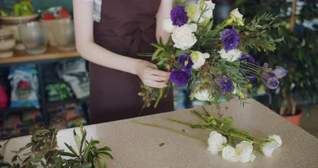 продавщица : Creative female florist is making beautiful bouquet holding bunch of flowers in shop arranging colorful plants indoors. People, work and small business concept.
