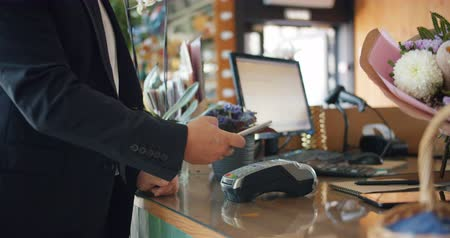 продавщица : Male customer is paying with smartphone making online payment then taking bunch of flowers from florist in store. Modern technology and finance concept. Стоковые видеозаписи