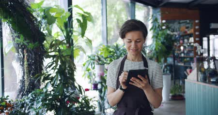 floriculture : Pretty female florist is counting plants entering records in tablet busy with work working in shop walking around smiling. People, business and job concept.