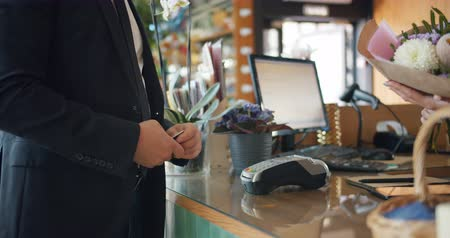 продавщица : Slow motion of customer paying with bank card then taking bouquet of flowers from female florist in floral store. Business, people and technology concept.