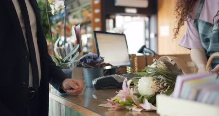 caixa : Man purchasing flowers paying with cash dollars in florists store giving money to cashier taking bouquet from saleswoman. Commerce, business and people concept.