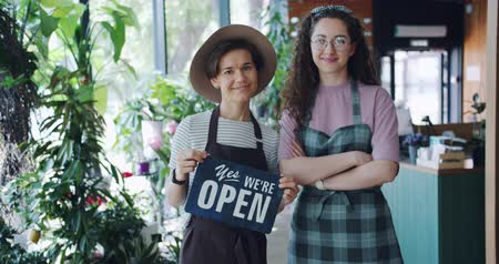 slate : Slow motion of beautiful women coworkers holding we are open sign standing in flower shop together smiling looking at camera. Small business and people concept. Stock Footage