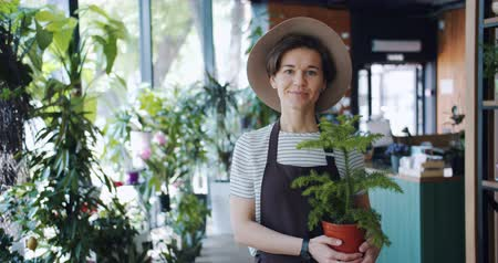 retailing : Slow motion portrait of cute young lady in apron and hat holding potted plant in florists store smiling looking at camera. Business, people and houseplants concept.