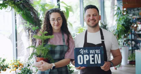 slate : Man and woman business owners are holding we are open sign and green potted plant standing in flower shop welcoming buyers. People and start-up concept.