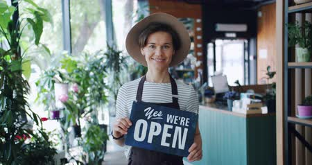 slate : Portrait of charming girl in apron and hat holding yes we are open sign welcoming people to new flower shop looking at camera smiling. Youth and business concept.