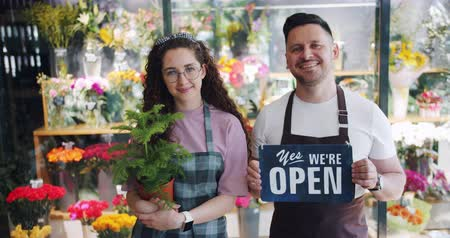 retailing : Employees of floral shop man and woman holding open sign and green plant standing near beautiful blooming flowers together. Youth and small business concept. Stock Footage